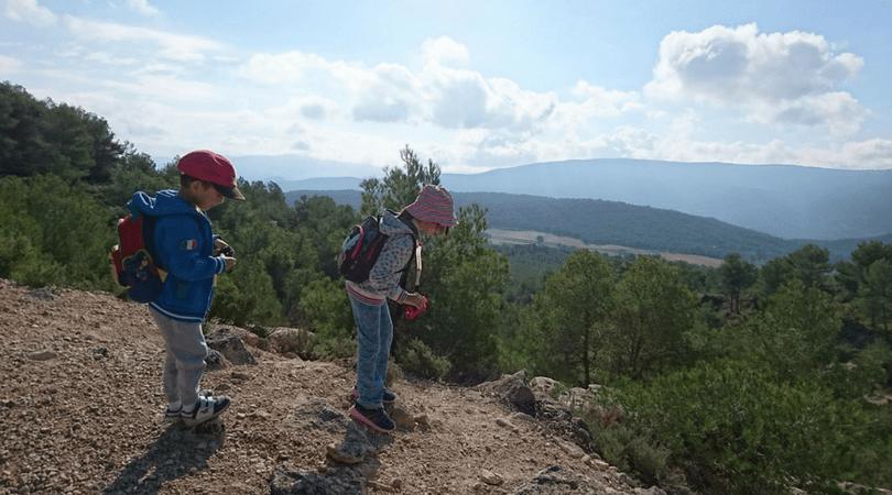 ruta a la buitrera de Alcoy peques mirando el valle con los niños en la mochila