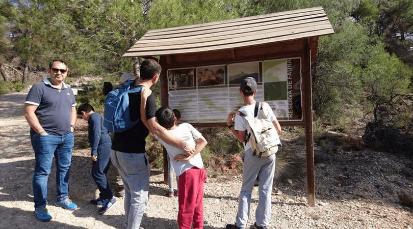 ruta a la buitrera de Alcoy panel informativo con los niños en la mochila